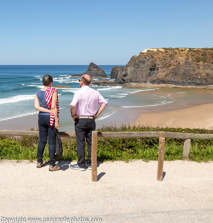 Couple standing looking out over the coastline view of headlands and bay with wide sandy beach, Praia de Odeceixe, Algarve, Portugal, Southern Europe