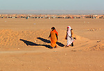 Two women walk on December 14, 2003, in the Saharawi refugee camps. Saharawi people have been living at the refugee camps of the Algerian desert named Hamada, or desert of the deserts, for more than 30 years now. Saharawi people have suffered the consecuences of European colonialism and the war against occupation by Moroccan forces. Polisario and Moroccan Army are in conflict since 1975 when Hassan II, Moroccan King in 1975, sent more than 250.000 civilians and soldiers to colonize the Western Sahara when Spain left the country. Since 1991 they are in a peace process without any outcome so far. (Ander Gillenea / Bostok Photo)