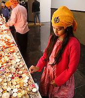 Nederland  Amsterdam 2016. Divali viering in de Shri Guru Nanak Gurdwara Sahib, een tempel van de Sikhs. Het Sikhisme is een onafhankelijk geloof dat geïnspireerd is op het hindoeïsme maar een eigen religieuze identiteit heeft. Meisje steekt een kaarsje aan.  Foto Berlinda van Dam / Hollandse Hoogte
