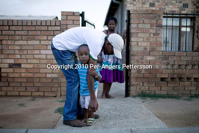 SOWETO, SOUTH AFRICA - JANUARY 15: Thami Nkosi, a 29-year old activist, plays with his son Tumi on January 15, 2010, in Soweto, South Africa. Thami is a gender justice activist and often counsels men how to use condoms and not to cheat or abuse women. He is part of the new young generation of black South African's who has got better education opportunities. Soweto is the largest township in South Africa, located about 10 kilometers southwest of downtown Johannesburg. The population is estimated to be around 2-3 million. (Photo by Per-Anders Pettersson/Getty Images)