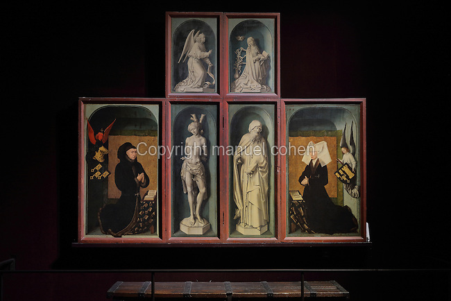 Closed panels of the polyptych altarpiece, with Nicolas Rolin and Guigone de Salins kneeling in prayer, and tromple l'oeil paintings of the Annunciation,  St Sebastian (patron saint of the chancellor) and St Anthony (patron saint of the Hospices and of Guigone de Salins), 1446-52, by Rogier van der Weyden, 1399-1464, commissioned by Nicolas Rolin in 1443, in Les Hospices de Beaune, or Hotel-Dieu de Beaune, a charitable almshouse and hospital for the poor, built 1443-57 by Flemish architect Jacques Wiscrer, and founded by Nicolas Rolin, chancellor of Burgundy, and his wife Guigone de Salins, in Beaune, Cote d'Or, Burgundy, France. The altarpiece was originally in the Chapel, but is now in the museum. The panels were only opened to patients during holy days. The hospital was run by the nuns of the order of Les Soeurs Hospitalieres de Beaune, and remained a hospital until the 1970s. The building now houses the Musee de l'Histoire de la Medecine, or Museum of the History of Medicine, and is listed as a historic monument. Picture by Manuel Cohen