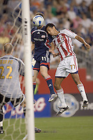 Pat Noonan (Revolution, blue) heads a ball on net as Orlando Perez (Chivas USA, striped) defends and Preston Burpo reacts from the line.  New England Revolution tied Chivas USA, 1-1, at Gillette Stadium on July 7, 2007.