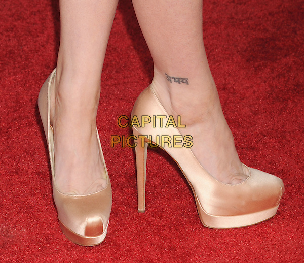 "Brittany Snow's shoes .arriving at the World Premiere of ""Ted"" at Grauman's Chinese Theatre in Hollywood, California, USA, .June 21st, 2012. .detail feet platform heels tattoo on ankle   silk satin gold beige shoes  .CAP/ROT/TM.©TM/Roth Stock/Capital Pictures"