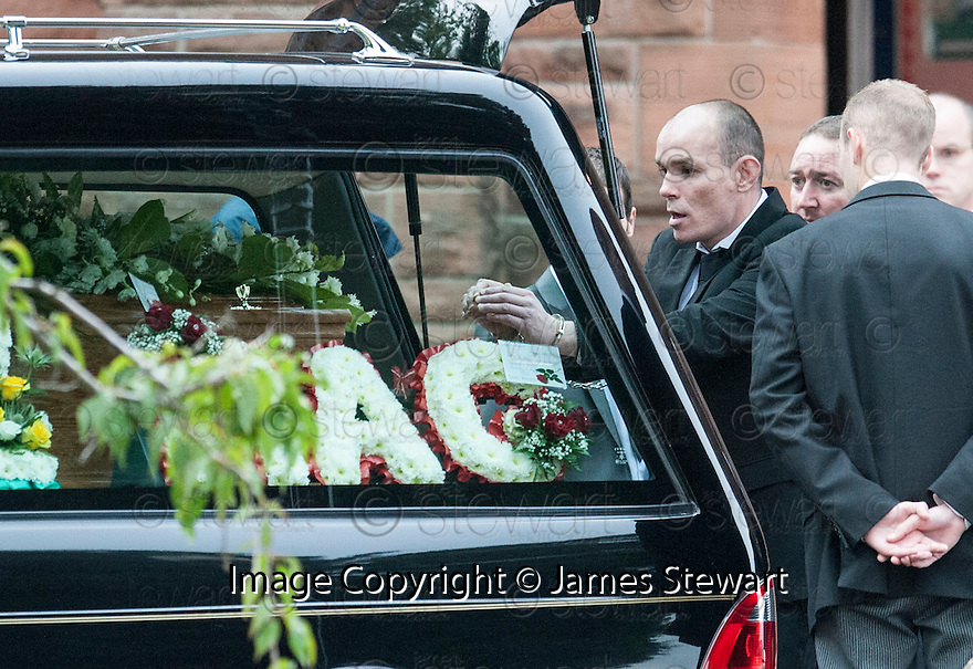 Hugh Haney, still handcuffed to a G4S officer reaches in to the coffin of former crime family matriarch Mags Haney at St Mary's RC Church in Stirling.