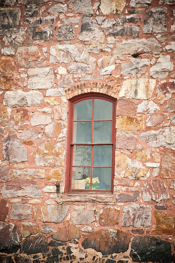 A window in a stone building in downtown Ishpeming Michigan.
