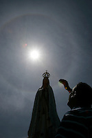 Pilgrim reacts with  statue of Our Lady of Fatima  during the procession  of Fatima in central Portugal.