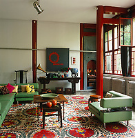 The living room of this converted factory is furnished with a contemporary L-shaped sofa and Chinese tables and accessories with the structural columns painted in red lacquer