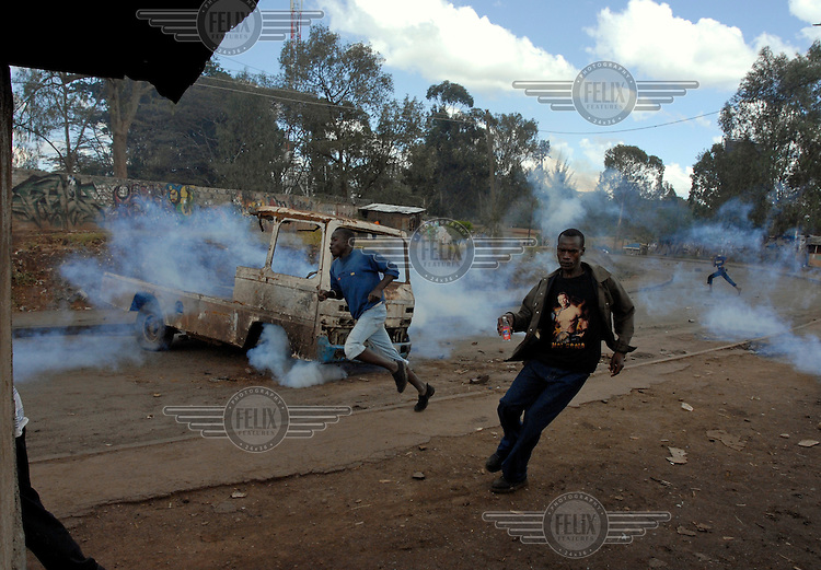 Protesters run from tear gas fired by police during riots in the Kibera slum. Later that evening four people were shot by police. Supporters of the opposition Orange Democratic Movement (ODM), who are popular in Kibera, were leading protests against disputed election results.