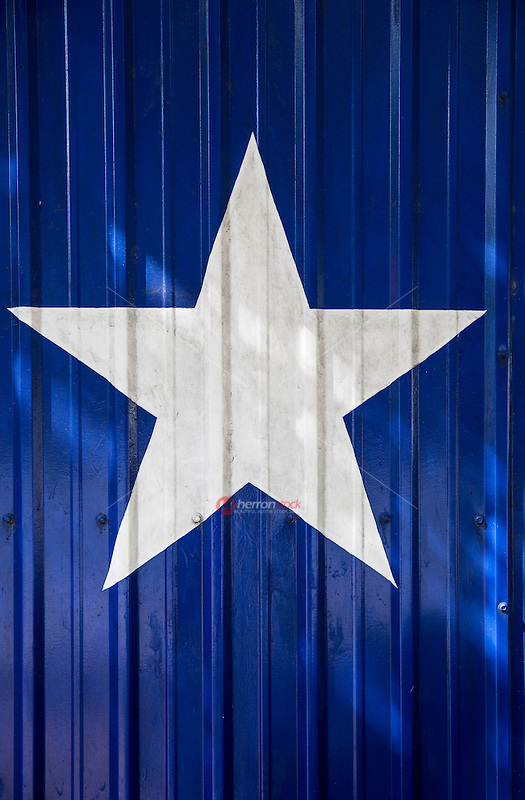 The Lone Star is a symbol of the State of Texas. Pictured here,  the Texas Lone Star is painted on tin building, white star on a blue background - Stock Image.