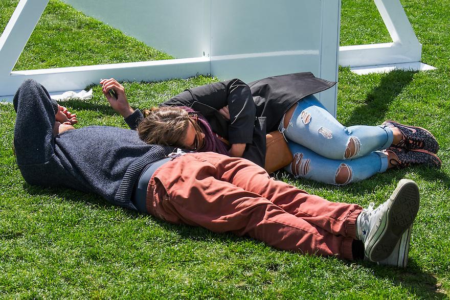 Nederland, Amsterdam, 30 mei 2015<br /> Museumplein. Stelletjes liggen in het gras van het Museumplein. Toeristen zijn moe van het slenteren door de stad. <br /> <br /> Foto: Michiel Wijnbergh
