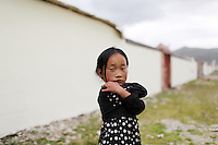 A Tibetan girl in a community on the Tibetan Plateau, in western China. Relocation communities been created to house nomadic herders moved from the highland grasslands. The nomads have been blamed for contributing to the deterioration of the grasslands, so have been moved, sometimes forcibly, into newly built towns that can be found across the plateau.