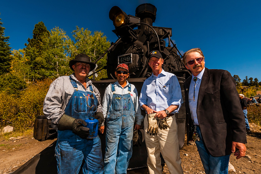 Hickenlooper with C&amp;TSRR President John Bush and train crew<br />  aboard the Cumbres &amp; Toltec Scenic Railroad train, during a visit riding from Antonito to Osier, Colorado. The Cumbres &amp; Toltec Scenic Railroad has been jointly owned by the States of Colorado and New Mexico since 1970 when it was purchased from the Denver and Rio Grande Western Railway, which was going to scrap the line. The train makes a 64 mile run between Antonito, Colorado and Chama, New Mexico. The railroad is the highest and longest narrow gauge steam railroad in the United States with a track length of 64 miles. The train traverses the border between Colorado and New Mexico, crossing back and forth between the two states 11 times. The narrow gauge track is 3 feet wide. It runs over 10,015 ft (3,053 m) Cumbres Pass.