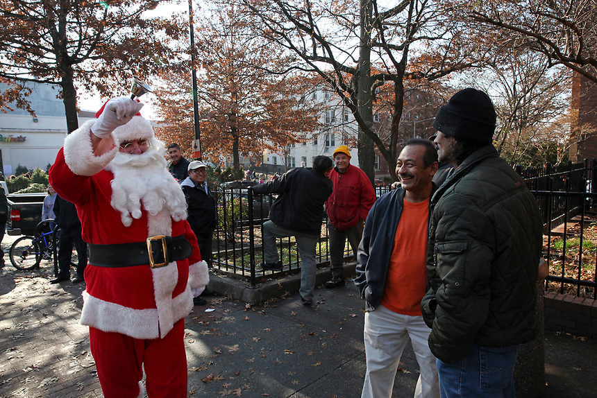 (171203RREI2594) Santa Claus greets the men on the corner on Mt. Pleasant Holiday Festival day.  La Esquina Documentary Project. Latinos have gathered near the 7 - 11 at the corner of Mt. Pleasant St. and Kenyon St. NW. for more than 40 years.  Washington DC. Dec. 2 ,2017 . ©  Rick Reinhard  2017     email   rick@rickreinhard.com