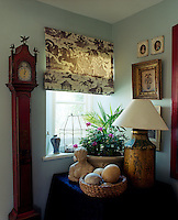 Next to an elegant antique grandfather clock in the entrance hall a circular table displays a bowl of ostrich eggs, a small carved sculpture and an arrangement of geraniums