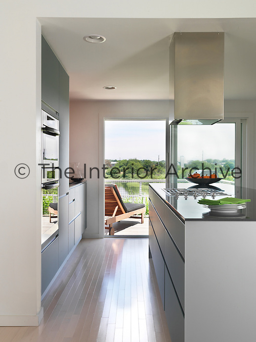The modern kitchen opens onto a decked balcony with great views over Salt pond, Rhode Island
