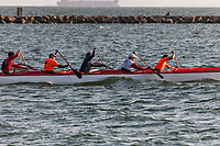Six person crews work in unison to propel outrigger canoes through the water at the Seaplane Lagoon near the former Naval Air Station Alameda on San Francisco Bay.