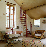 A spiral staircase in one corner of the studio which was once a cow byre