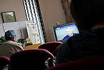 Patients watch a live broadcasting of a news conferece given by the chairman of Tepco, the company operating  the nearby Fukushima No. 1 nuclear power plant, in the waiting room of a clinic in Minami-Soma, Fukushima Prefecture, Japan on 30 March, 2011.  Photographer: Robert Gilhooly