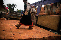 Workers transfer bricks from a truck to the roadside in Xinjie, Yuanyang County, Yunnan Province, China.