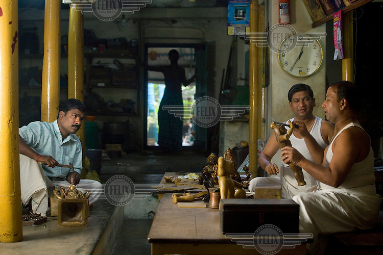 Master craftsmen Radhakhrishna Sthapathy (far right) and his brother Srikanda (near right) mould an icon in wax in the S. Devasenapathy Sthapathy and Sons bronze casting workshop. The current Sthapathy generation is the twenty-third generation of bronze casters. Their method using the lost-wax process remains unchanged to this day.