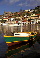 "AJ2529, Grenada, Caribbean, St. George's, Caribbean Islands, Green fishing boat anchored in the calm waters of the harbor with a scenic view of St. George's the capital city on the island of Grenada """"the spice isle"""" (a British Commonwealth member)."