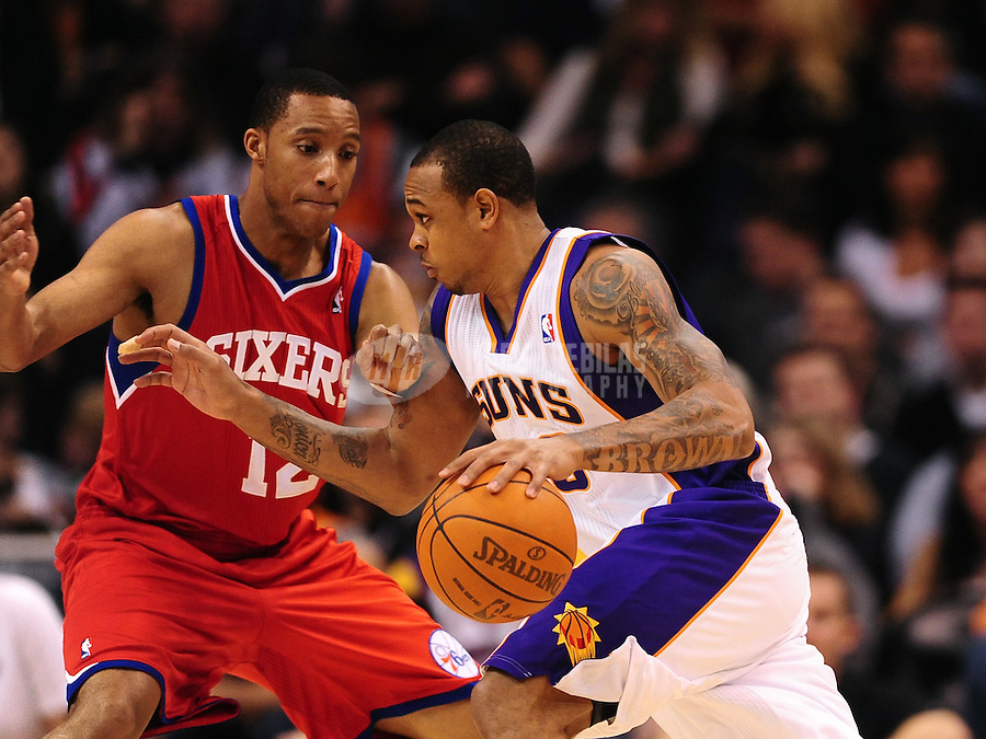 Dec. 28, 2011; Phoenix, AZ, USA; Phoenix Suns guard Shannon Brown (right) drives to the basket against Philadelphia 76ers guard Evan Turner at the US Airways Center. The 76ers defeated the Suns 103-83. Mandatory Credit: Mark J. Rebilas-USA TODAY Sports