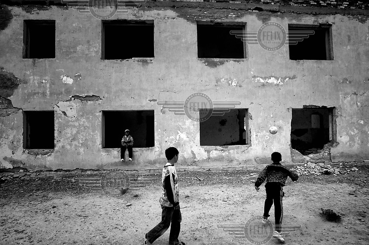 Young boys playing football near an abandoned house. During the 1950s and the 1960s the rivers that feed the Aral Sea (the Amu Darya and the Syr Darya) were diverted for irrigating cotton and other crops. This caused the lake to shrink uncovering sediments heavily polluted with industrial fertilizers that were washed into the lake over the preceding decades. Without the lake's water to contain it these toxic particles were spread by the wind and have caused numerous health problems in surrounding communities. Furthermore, as the lake evaporated the remaining water became increasingly saline and unable to sustain life, destroying the fishing industry. Muynak, once a thriving fishing port, became a depressed and dusty town far from the receding shore.