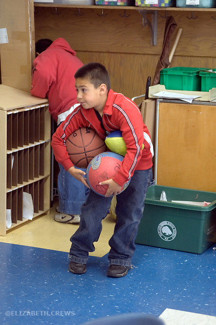 Oakland CA 2nd grade ball monitor getting ready for ball play at recess