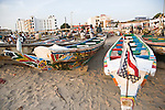 Colorfully painted fishing boats line the beach at this fish market in Dakar, Senegal.  One of the boats displays a flag reminiscent of the American flag.