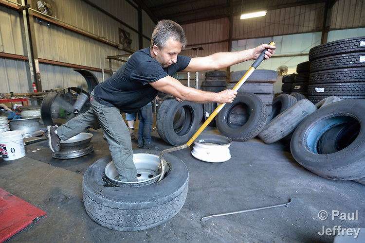 Valerii Chronoblavskyi, a resettled refugee from Ukraine, works in a tire shop in Harrisonburg, Virginia, on July 18, 2017. He was resettled in the community by Church World Service. <br /> <br /> Photo by Paul Jeffrey for Church World Service.