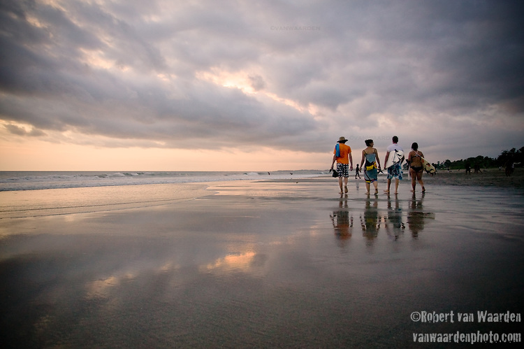 Four surfers walk down Kuta beach in Indonesia as the sun sets