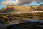 Late afternoon light on beach and cliffs La Caleta de Famara, Lanzarote, Canary islands, Spain