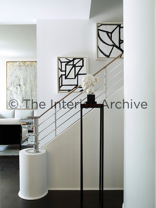 In the entrance hallway, the staircase, with its Art-Deco inspired handrail, is a custom design and the floors are stained oak. The painting in the stairwell is by Al Held.