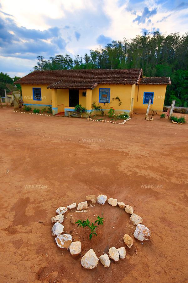 Bresil, etat Minas Gerais, Muzambinho (Nord de Sao Paulo), 30 octobre 2012.<br /> <br /> Fazenda (ferme, exploitation de cafe) Nossa Senhora da Aparecida  ( Notre-Dame de l&rsquo;Apparition ), membre du programme Nespresso AAA&nbsp; : un plant de cafeier ceint d'un collier de pierres devant une maison d'ouvriers agricoles.<br /> La fazenda possede des logements, petites maisons ouvrieres situees dans l'enceinte de la propriete agricole, qu'elle loue a ses ouvriers.<br /> Reportage les Chants de cafe_soul of coffee, realise sur les acteurs terrain du programme de developpement durable Triple AAA de Nespresso.<br /> <br /> Brazil, Minas Gerais, Muzambinho, (North of Sao Paulo), October 30, 2012 <br /> <br /> Fazenda (a coffee farm within a plantation), Nossa Senhora da Apareida (Our Lady of Aparecida), a member of the Nespresso AAA program: A coffee tree plant surrounded by a ring of stones in front of a farm laborers home. The fazenda owns small houses on the property that are available to the workers. <br /> Assignment: les Chants de cafe_ Soul of Coffee, implemented on the fields of Nespresso&rsquo;s AAA Sustainable Quality Program.