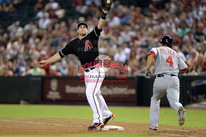 Arizona Diamondbacks first baseman Paul Goldschmidt (44) takes a throw as Zach Walters (4) runs to the bag during a game against the Washington Nationals at Chase Field on September 28, 2013 in Phoenix, Arizona.  Washington defeated Arizona 2-0.  (Mike Janes/Four Seam Images)