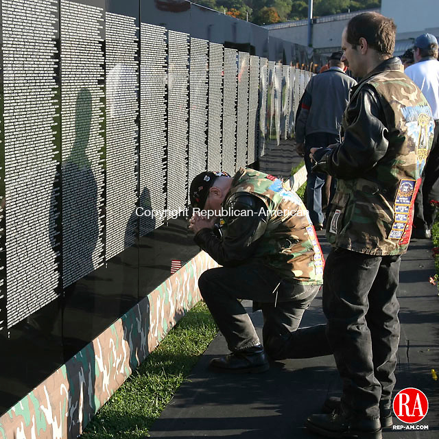 SHELTON, CT- 12 OCTOBER 2006 101206BZ10- U.S. Army Vietnam War veteran Al Beck, of Milford,  kneels at the base of a panel containing the name of his childhood friend Kenneth Cushen while visiting The Moving Wall on The River Walk in Shelton Thursday afternoon.  Beck's son, Al Beck Jr. stands at right. The wall is a 1/2 scale replica of the Vietnam Veterans Memorial in Washington D.C.<br /> Jamison C. Bazinet Republican-American