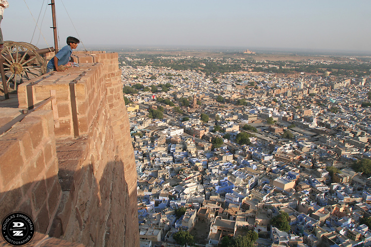A visitor to Meherangarh, the fort of the maharaja of Jodhpur, leans over for a view of the city below.  Meherangarh fort sits atop of a125 meter high hill in the center of the city and  dominates the skyline of the city of Jodhpur, India, which sprawls below the fort as a mass of cubist shapes, most painted blue.  Photograph by Douglas ZImmerman
