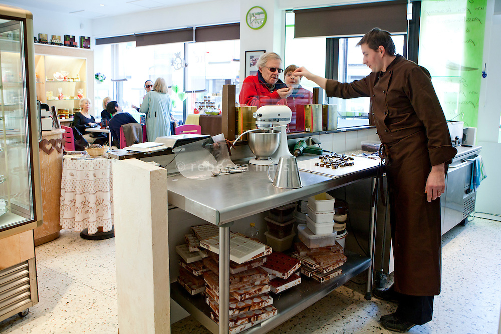 Chocolatier Patrice Arbona gives customers a taste of chocolates he is making his shop 'Entre Mes Chocolats', Vence, France, 10 February 2011