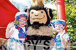 Alva Joyce and Maeve Gaffney cuddles up with King Puck's mascot during the parade in Killorglin on Sunday