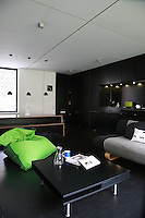 This open plan living area consists of a black-painted kitchen, a black dining table and a low-level seating area, united by a black tiled floor