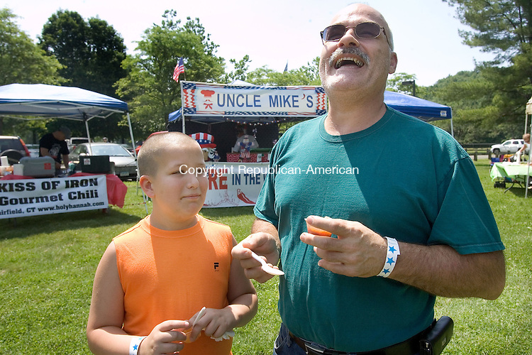 WOODBURY CT. 22 June 2013-062213SV12-From left, Anthony Vitone, 10, of Oakville shares a laugh with his grandpa James Godin of Plainville while sampling chili at the Chili cook off at Hollow Park in Woodbury Saturday. The Animal Rescue Foundation from Plymouth and the Woodbury DARE Program sponsored the event.<br /> Steven Valenti Republican-American