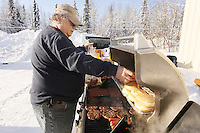 "February 16, 2013  A volunteer since 1986, Larry Cheeso cooks hot dogs and burgers outdoors for pilots and other volunteers at the Willow airport on the first day of the ""Food Fly"" as musher food, straw, HEET and people food is flown to the 4 checkpoints on the east side the Alaska Range. ..Photo Copyright Jeff Schultz  -- Do not reproduce without written permission"