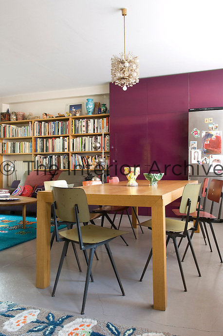 One wall of this open-plan living/dining area is taken over for storage with a floor-to-ceiling bookcase and cupboard painted purple
