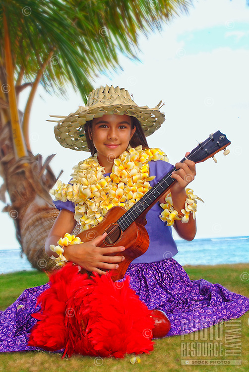 Keiki hula dancer with ukulele and an uliuli at the beach.