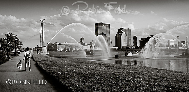 Walking the dog at Deeds Point with view of Dayton Ohio skyline through fountains