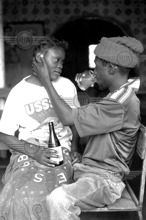 ©Giacomo Pirozzi/Panos Pictures..Zambia. Lusaka. A young man drinks a beer with a girl in the Jazz Club in George Compound, one of the city's largest shanty towns. Volunteer peer educators distribute condoms and give advice in bars like this one.