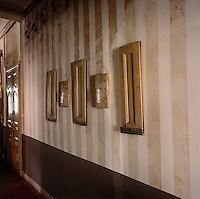 Pieces of wooden artwork are hung in a hallway with a painted striped finish.