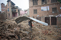A man carries a canopy recovered from his destroyed house in Shanku near Kathmandu, Nepal. May 9, 2015