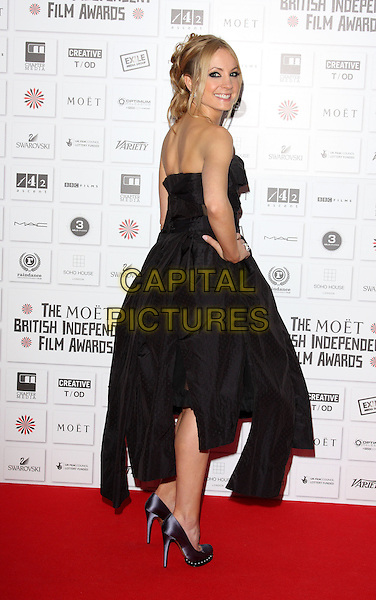 JOANNE  FROGGATT  .Attending the Moet British Independent Film Awards 2010 held at Old Billingsgate, London, England, UK, December 5th 2010..full length strapless black dress hand on hip Vivienne Westwood gown shoes ruched back rear behind over shoulder CAP/ROS.©Steve Ross/Capital Pictures.