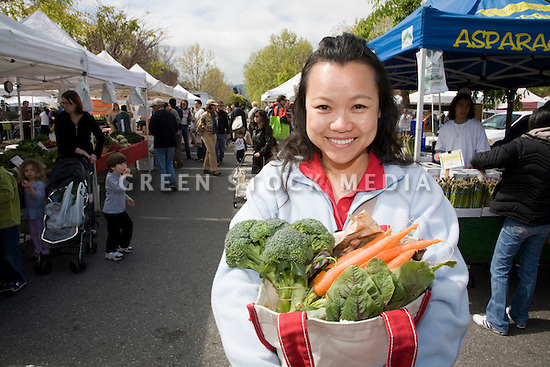 A mid-adult woman (30-40 years) holding fresh produce in reusable shopping bag at a local farmer's market. The market is held every Sunday in Mountain View, California, USA